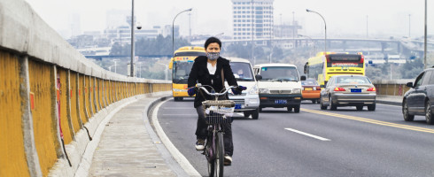 Chinese woman riding bike on busy street
